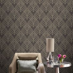 This stunning Astoria Deco wallpaper features an eye-catching geometric art deco style pattern in silver with soft gold undertones, with a subtle mica sheen and glitter highlights. This is embedded onto a matte charcoal grey background with a soft textured finish.
