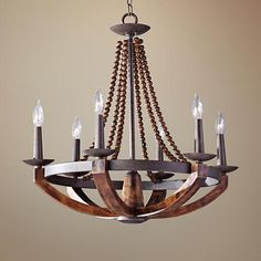 This round transitional six-light chandelier is inspired by classic Old World designs and updated with beading and warm faux wood finish.