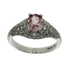A padparadscha sapphire and diamond multi-stone dress ring consisting of a principal padparadscha sapphire in an 18ct white gold 4-claw setting surrounded by diamonds pave set into the shoulders and mounted on a plain 18ct white gold shank.