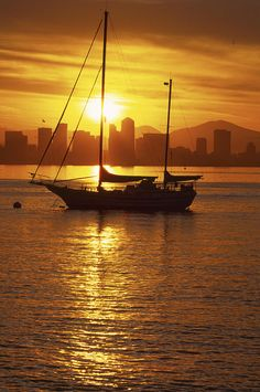 Silhouetted sailboat at sunrise with San Diego skyline in distance
