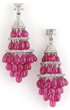 A pair of Art Deco cabochon ruby and diamond chandelier earrings. Each designed as two half-hoop rows of drop-shaped ruby cabochons, between rose-cut diamond spacers, to a graduated cluster of ruby cabochons, suspended from a t-shaped baguette diamond and graduated rose-cut diamond surmount, circa 1920, post and alpha fitting. #ArtDeco #earrings