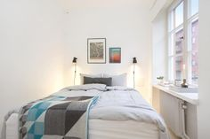 Simple hanging wall lamps provide reading light to each side of the bed in this small room.