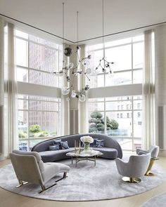 The floor-to-ceiling windows of this double-height Tribeca triplex by Amy Lau highlight the Lindsey Adelman chandelier. The Vladimir Kagan sofa and pair of swivel chairs are custom.
