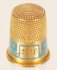 A Fabergé gold and champleve enamel thimble, St. Petersburg, circa 1900. Of traditional form with a turquoise enamel Greek-key design band.