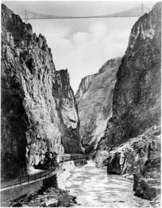 Royal Gorge, granite canyon of the Arkansas River, Fremont County, Colorado; Denver and Rio Grande Western Railroad narrow gauge passenger train runs along river; hanging suspension bridge in distance above river; hand drawn toll bridge at top of canyon.  Date between 1927 and 1931