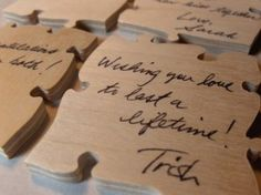 Purchase a wooden puzzle and scatter pcs out on guests' tables for them to sign. Keep it as a game or reassemble and coat it with a sealant to be used as a wall decoration