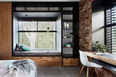 The steel windows on the exterior of this modern house also push into the bedrooms, where futon mattresses are used as day beds to create the ideal built-in nook.