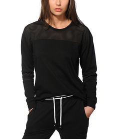 A classic style gets a modern twist with this solid black crew neck sweatshirt that features a slight high low hemline and mesh panel detailing at the shoulders and sleeves.