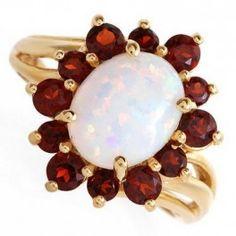 10K Gold Ring w Garnet & Opal Size 7  Material: 10K yellow gold  Gemstones: 12/1.20ct genuine garnet  Gemstones: 1/2.75ct created opal  Width: 17mm