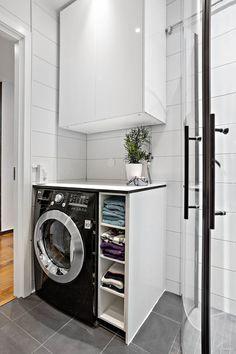 Kombinerad tvättmaskin/torktumlare i badrummet. Här finns också inbyggda högtalare i taket. Vita högblanka plattor i kombination med grå plattor ger snygg finish.