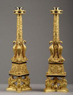 Une paire de grands bougeoirs en bronze doré reposant sur une base tripode formée de trois lions ailés. Ornés de têtes de bélier, d'oiseau et de feuilles et fleurs...