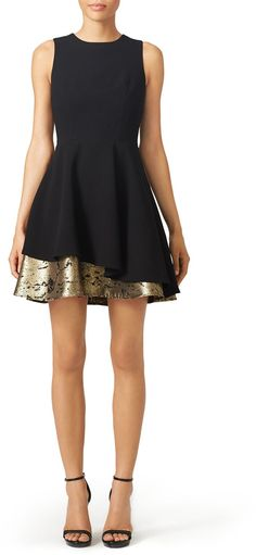 Sleek black dress with an assymetrical touch of gold.