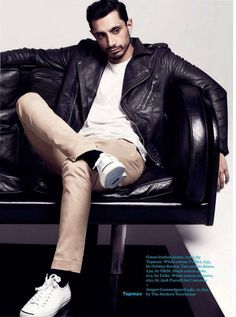 Riz Ahmed, asymmetrical leather biker jacket, white crewneck t shirt, khakis, white leather Jack Purcell sneakers, weekend