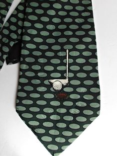 A wonderful vintage 1995, Nicole Miller, 100% silk hand sewn men's necktie showing off white golf clubs and balls amidst ivy green ovals on a black