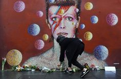 Mourners left flowers at a mural of David Bowie in Brixton, the London neighborhood where he was born, on Monday.