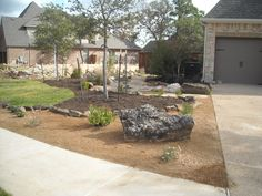 Front yard landscape - Xeriscape theme with decomposed granite, mulch, a dry creek bed and walkway, a beautiful specimen boulder and native plantin…