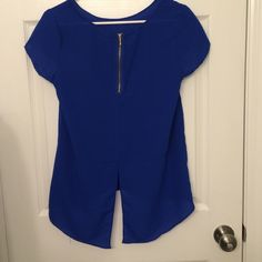 Blue Polyester Shirt Blue high/low polyester short sleeve shirt with playful back. Hits at the hips in the front and low on the back. The zipper and slit are on the back of the shirt! Never worn. No stains or holes. True to size. Tops Blouses
