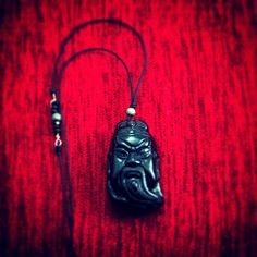 Worldwide Inspirations    A hand crafted pendant of an obsidian Samurai head binded with  spinel minerals and silver.