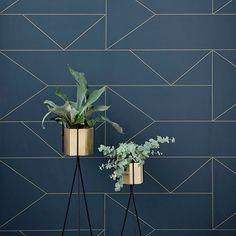 Lines de Ferm Living est un papier peint intissé inspiré par l'époque Art Déco. On retrouve un fond recouvert d'un bleu foncé profond et de lignes dorées brillantes.