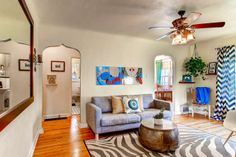 Love this eclectic mix of modern art and chevron curtains with the arched doorways and hardwood floors!