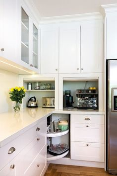 Stylish, open corner shelves replace the traditional drawers in this kitchen [Design: Kitchens by Peter Gill]