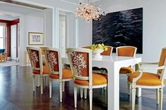 Embroidered fabric on chair backs, an oversized herringbone pattern in the wood floor, and a custom-made table sheathed in parchment lend quirky elegance to the dining room. The Met chandelier is by Lobmeyr, the painting is by Karen Gunderson, a nod to the home's view of Lake Michigan.