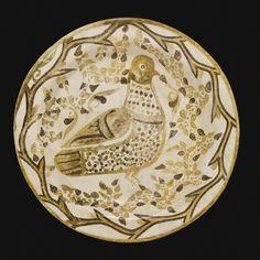 A Rare Abbasid Bichrome Lustre Plate with a bird in foliage, Iraq, 9th century