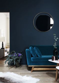 Elegant living room in blue tones with eucalyptus decorations and a velvet couch.