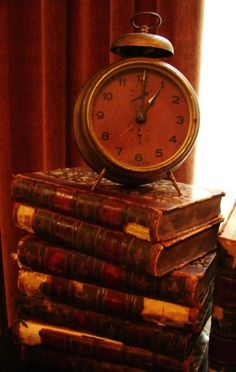 Antique alarm clock on book pile