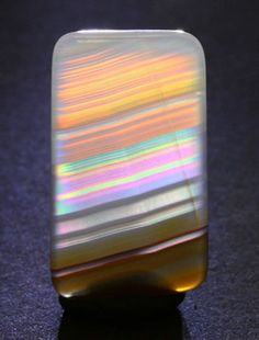 An enlarged view of the iris agate specimen with backlighting. This view is at a slightly different angle than the other backlighted view also pinned. It demonstrates that the spectral colors change with the angle of incident light and observation.