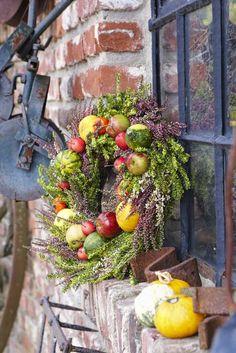 Der Herbst ist Erntezeit. Leuchtende Früchte wie Äpfel und Zierkürbisse wurden auf einen locker gebundenen Heidekranz montiert.