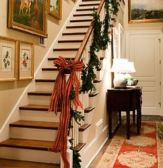 Staircase garland with a bow for a homey Christmas feel.