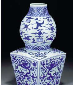 BLUE AND WHITE SHENG VASE, JIAJING SIX CHARACTER MARK TO BASE, with pear-shaped upper section, narrow waist and tapering square lower section, painted with shaped panels of writhing dragons amongst clouds on a ground of flower sprays, the shoulder with cloud motifs, the upper section with crane in flight amongst cloud scrolls and trigrams, the neck with character roundels on a geometric pattern ground — 14 3/8in. (36.5cms) high.
