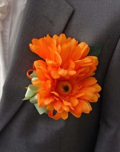 Grooms artificial orange Wedding buttonhole with two   gorgeous orange gerbera's.   A spray of lush green fisus leaves and a grosgrain  two tone bow in apple green and orange.