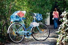 Un vélo peint en bleu à pois blancs avec panier à boutons, caisse et selle assortis.
