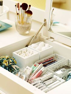 Organize a makeup and jewelry station with modular containers, use tine fabric sacs for jewelry, and fill a vase with sand to hold makeup brushes