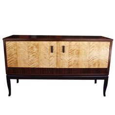 Swedish art deco era sideboard composed of highly figured golden flame birch with rosewood banding. Base in ebonized birch wood.   Cabinet in stained birch wood. Pulls in ebonized birch wood.   Single cavity interior cabinet with removable shelf. 1930s