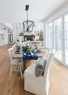 Lake House Blue and White Living Room Decor. Large windows, paneled walls and ceiling beams with blue and white decor and warm wood tones. Estilo Navy, Blue And White Living Room, Living Comedor, Christmas Table Settings, Dining Room Inspiration, White Decor, Dining Room Table, Living Room Decor, Decoration