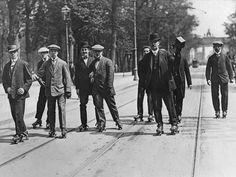wazzup2!Gut in Fahrt, auch im Anzug: Das Brandenburger Tor im Rücken, üben diese Herren sich im Tiergarten im Rollschuhlaufen. Die Aufnahme entstand im Jahr 1909