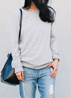 Andy Heart is wearing a grey sweater from Everlane, distressed jeans from Frame Denim and a bucket bag from Mansur Gavriel