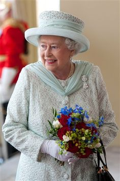 with a rare smile caught on camera. Britain's Queen Elizabeth II holds a bouquet of flowers a... CARL COURT / AP