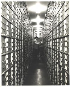 An archivist at work in the FDR Library archival stacks, circa 1950s. The document boxes were designed by FDR