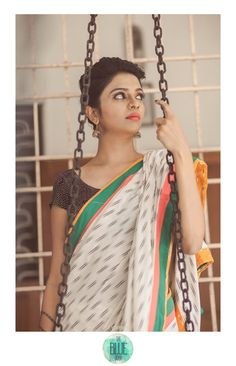 This cotton saree with a pink and green border and a yellow reverse border embellished with tassels.For details,contact- bluedoor.the@gmail.com