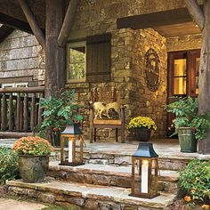 ❥ Stone Porch. Randomly placed stepping-stones crafted from local granite lead to this front porch's wide steps. Hand-hewn posts and railings, along with graceful brackets, are crafted from regionally harvested locust wood to further enhance this cottage's connection to the land. Local fieldstone clads the porch walls.