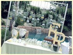 cute ideas- initials in big letters with a photo table of the bride to be. Milk bud glass vases.