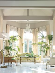 The solarium's features a twenty-foot ceiling and French doors, accented by a palm motif chosen for panache and a bit of tropical chic.  Chair, McGuire, and sofa, Michael Taylor Designs. Chandelier, tables, bergères, torchères and Barovier & Toso lamp, all vintage   - Veranda.com