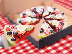 Watermelon fruit pizza. Thick slice of watermelon served with sliced strawberries, halved grapes (red and green), sliced banana and topped with shredded coconut