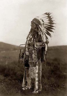 You are viewing a rare image of High Hawk. It was taken in 1907 by Edward S. Curtis.    The image shows High Hawk, standing, facing left, in ceremonial dress, war bonnet and holding a coup stick.    We have created this collection of images primarily to serve as an easy to access educational tool. Contact curator@old-picture.com.    Image ID# 6526AED6