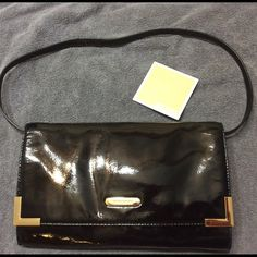 "Michael Kors Beverly Clutch NWOT Authentic Michael Kors oversized Beverly Black Patent Leather. Bought but never used its been sitting in my closet. Appears to have superficial scratch on gold trim. View pic. Selling at an excellent price due to that.  11.5"" Drop.Measures : 11.25 (L) x 7 (H) x 1.5 (D) Magnatic Snap Closure. Back Slip Pocket with snap closure.  Michael Kors signature lining with one zippocket, slip pocket & 6 credit card slots. Will consider all offers Michael Kors Bags…"