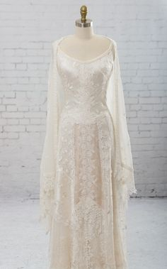 Diana by Martin McCrea   Sleeveless wedding dress with straps. Bodice of bias cut embroidered silk dupioni. The skirt is a collection of artfully arranged laces and trims. Includes shawl of embroidered chiffon and guipure lace.